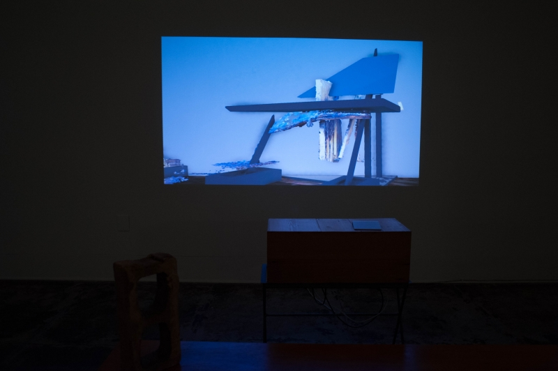 Image of digital artist justin wood's work about the john fava house. The image depicts a projected image against a wall of the artwork which is video game engine generated and depicts a ruined house.